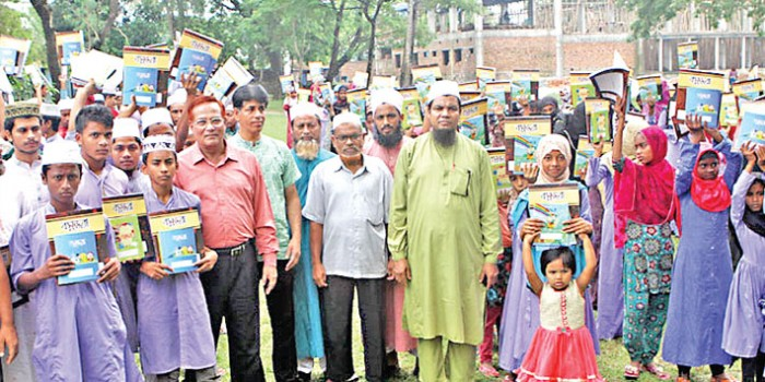 Students who received exercise books of Bashundhara brand pose with publisher of daily sun Maynal Hossain Chowdhury in Banchharampur on Wednesday.