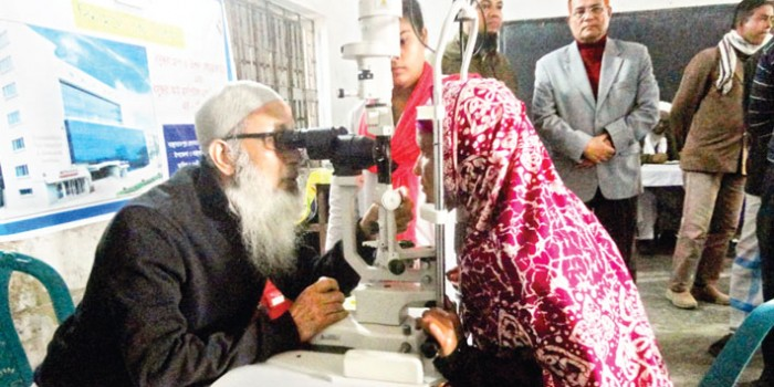 A woman is having her eyes tested at a free eye camp on Banchharampur Sobhania Islamia Alim Madrasa premises in Brahmanbaria on Tuesday. Bashundhara Group and Vision Care Foundation in association with Bashundhara Eye Hospital & Research Institute organised the event.