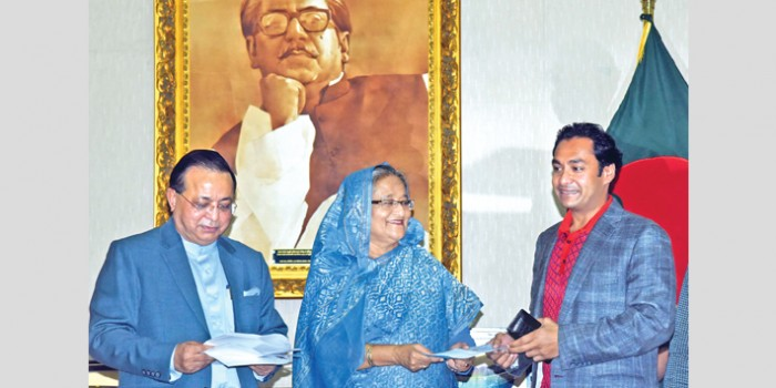 Bashundhara Group Managing Director Sayem Sobhan Anvir hands over a donation cheque to Prime Minister Sheikh Hasina at Ganabhaban in the capital on Monday